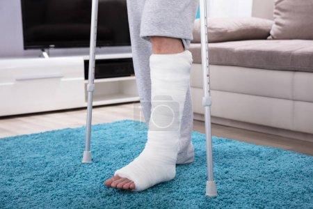 Foto de Hombre con pierna rota usando muletas para caminar en la alfombra azul - Imagen libre de derechos