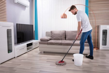Photo for Young Man Cleaning Floor With Mop At Home - Royalty Free Image