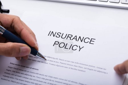 Close-up Of A Person's Hand Filling Insurance Policy Form