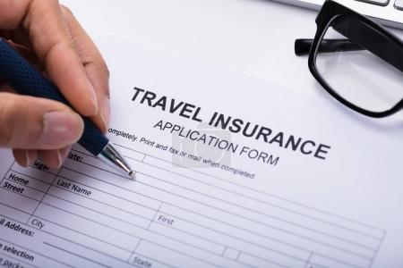 Close-up Of A Person's Hand Filling Travel Insurance Form