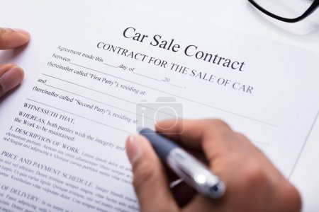 Close-up Of A Person's Hand Filling Car Sale Contract Form