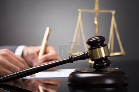 Close-up Of A Gavel In Front Of Judge Writing On Document