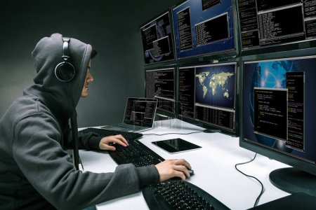 Rear View Of A Hacker Using Multiple Computers For Stealing Data In Office