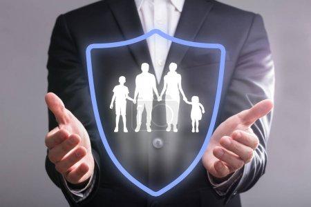 Photo pour Gros plan de main d'un homme d'affaires avec le bouclier protégeant la famille - image libre de droit