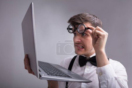Weird Man Looking At Laptop On Grey Background