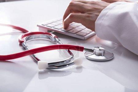 Doctor's Hand Typing On Keyboard Besides Stethoscope On White Desk