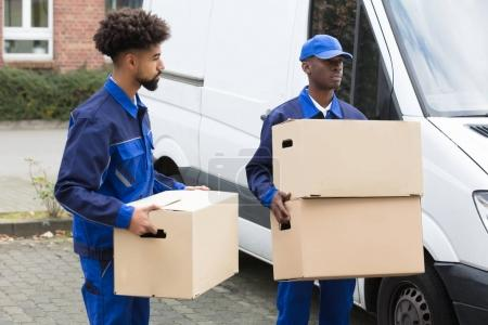 Photo for Close-up Of Two Delivery Men Holding The Cardboard Boxes - Royalty Free Image