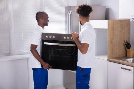Photo pour Deux travailleurs de sexe masculin en uniforme fixant le four dans la cuisine à la maison - image libre de droit