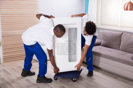 Two Young Male Movers Placing The White Cabinet On Wheel In The Living Room