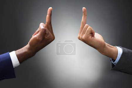 Two Businesspeople Showing Fuck Off With The Middle Finger Against Gray Background