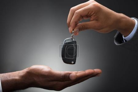 Close-up Of Hand Handing Car Key To The Person Against Gray Background