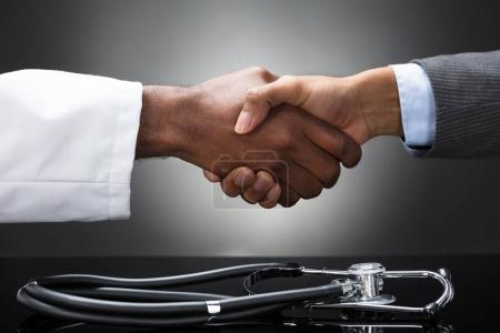Stethoscope On Desk In Front Of The Doctor And Business Man Shaking Hands