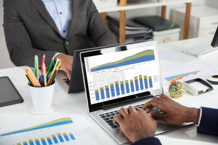 Photo pour Gros plan de deux hommes d'affaires utilisant un ordinateur portable pour analyser le graphique financier sur un bureau blanc - image libre de droit