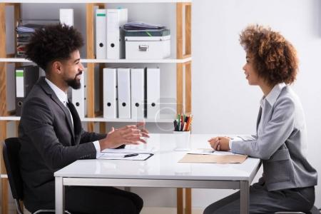Side View Of Two Young Businesspeople Having Conversation In Office