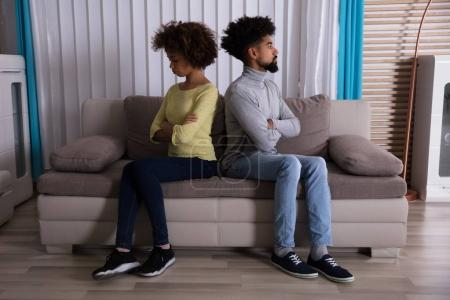 Unhappy Young Couple Sitting Back To Back On Sofa At Home