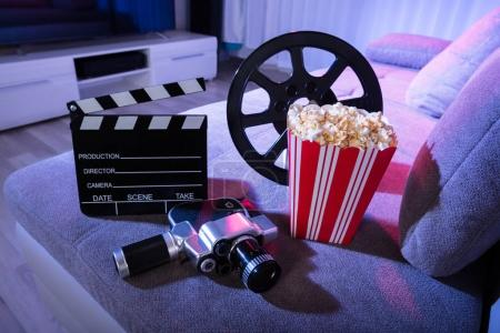 Close-up Of Movie Camera With Clapperboard And Popcorn On Couch At Night