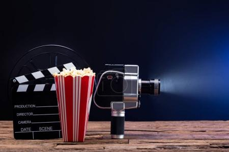 An Illuminated Movie Camera With Popcorn And Clapper Board Against Blue Background