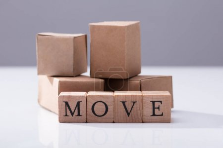 Close-up Of Move Text On Wooden Blocks In Front Of Cardboard Boxes