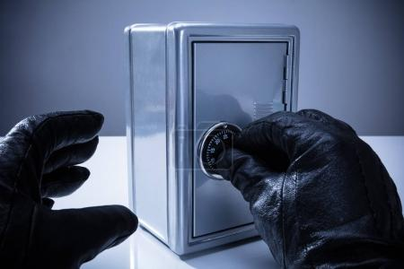 Close-up Of A Thief's Hand Wearing Gloves Unlocking Safe