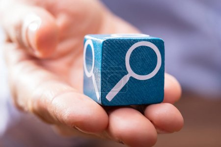 Close-up Of A Person's Hand Holding Wooden Block With Magnifying Glass Symbol On It