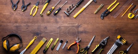 Overhead View Of Many Yellow Repair Tools Arranged On Wooden Table