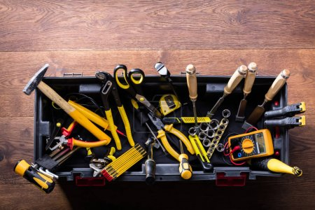 Photo for Overhead View Of Many Yellow Repair Tools Arranged On Wooden Table - Royalty Free Image