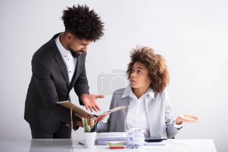 Jungunternehmer zeigt seiner Kollegin am Arbeitsplatz Fehler im Dokument