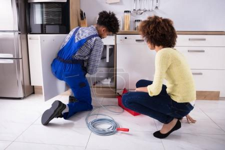 Woman Looking At Male Plumber Cleaning Clogged Pipes