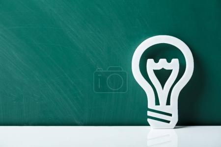Close-up Of A White Lightbulb Leaning On Green Chalkboard