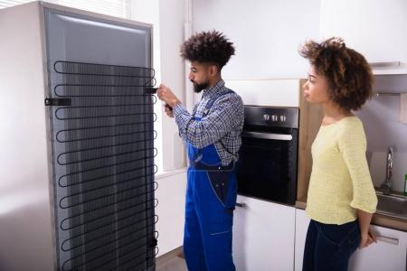 Woman Looking At Technician Repairing Refrigerator With Screwdriver In Kitchen