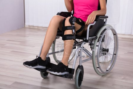 Female Patient With Knee Braces Sitting On Wheelchair