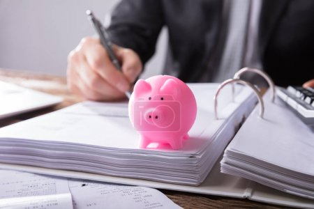 Close-up Of A Pink Piggybank In Front Of Businessperson Working On Documents