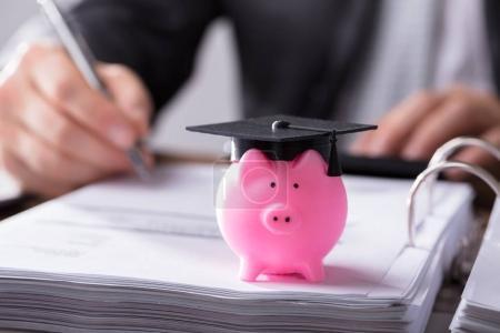 Close-up Of Pink Piggybank With Graduation Cap On Document