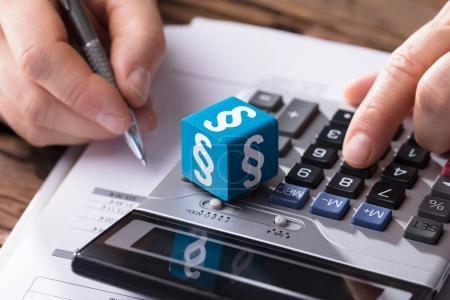 Photo pour Gros plan d'un dé montrant le symbole du paragraphe pendant que l'homme d'affaires calcule la facture avec la calculatrice - image libre de droit