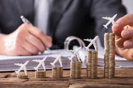 Photo pour Gros plan d'un humain plaçant un petit avion sur l'augmentation des pièces empilées sur un bureau en bois - image libre de droit