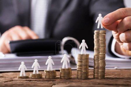 Foto de Mano humana comercialización pequeña figura humana creciente monedas apiladas sobre el mostrador de madera - Imagen libre de derechos