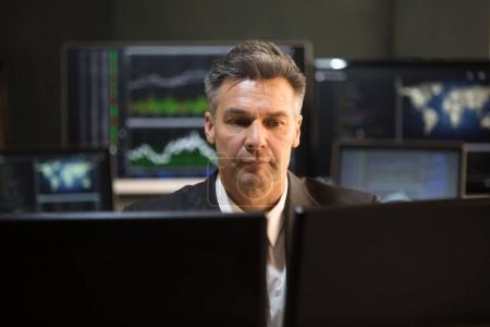 Mature Male Stock Market Broker Looking At Multiple Computer Screen In Office