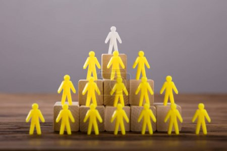 White Figure Standing On Top Of Yellow Human Figures Over Wooden Blocks