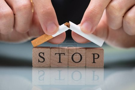 Close-up Of A Person's Breaking Cigarette Over Blocks Showing Stop Text