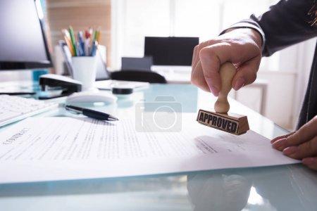 Photo pour Gros plan d'un homme d'affaires main estampage approuvé le contrat papier au bureau - image libre de droit