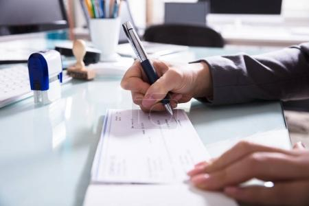 Close-up Of A Businessperson's Hand Signing Cheque...