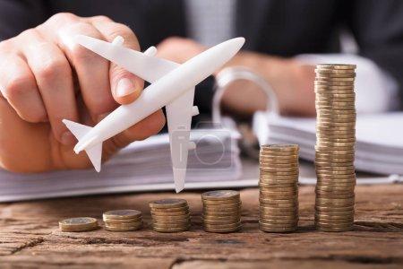 Photo pour Gros plan de l'avion volant à la main d'un homme d'affaires au-dessus de pièces empilées sur le lieu de travail - image libre de droit