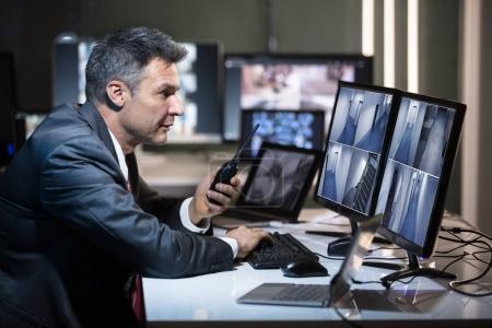 Photo pour Homme d'affaires parlant sur Walkie Talkie tout en regardant la caméra de vidéosurveillance sur plusieurs écrans d'ordinateur - image libre de droit