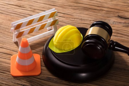 Gavel With Road Barrier, Hard Hat And Traffic Cone On Wooden Desk