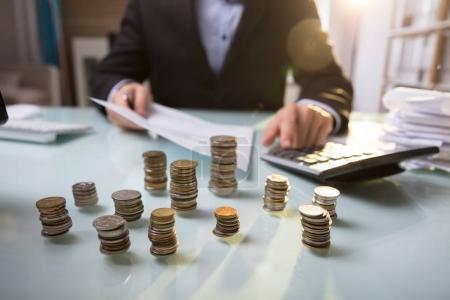 Photo pour Gros plan des pièces empilées devant un homme d'affaires travaillant sur un document - image libre de droit