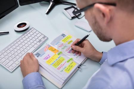 Businessman's Hand Writing Schedule In Diary With Pen At Workplace