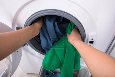 Close-up Of A Woman's Hand Putting Clothes In Washing Machine