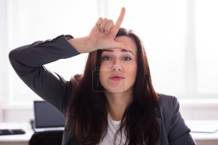 Businesswoman Showing Loser Sign With Fingers On Her Forehead