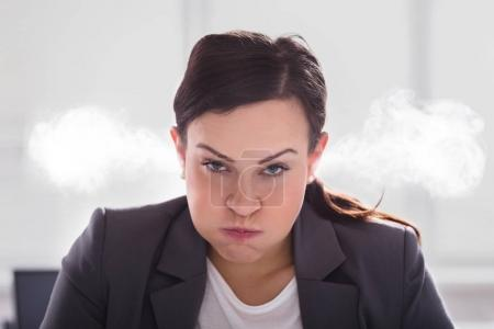 Portrait Of An Furious Businesswoman With Smoke Coming Out Of Her Ears