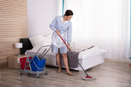Young Female Housekeeper Cleaning Floor With Mop In Bedroom